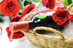 Red wine bottle with red roses stock photography