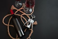 Red wine bottle, two glasses and corkscrew on black background. Top view with copy space stock photos