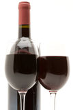 Red wine bottle with two glasses of red wine. On a white background stock photo