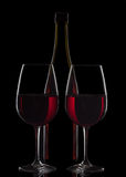 Red wine bottle and two wine glasses on black background.  royalty free stock photos