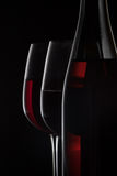 Red wine bottle and two wine glasses on black background.  stock photos