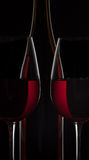Red wine bottle and two wine glasses on black background.  royalty free stock image