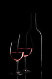 Red wine bottle and two wine glasses on black background on blac. K background stock image