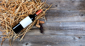 Red wine bottle with vintage wine corkscrew on straw and rustic Royalty Free Stock Photo