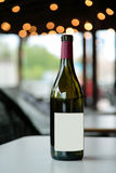 Red wine bottle on white table royalty free stock images