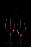 Red wine bottle and wine glass on black background.  royalty free stock image