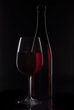 Red wine bottle and wine glass on black background.  stock image