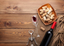 Red wine bottle, wine glass, bowl with corks and corkscrew Stock Photos