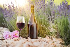 Wine over lavender field. Red wine bottle and wine glass on the ground. Sunset over a summer lavender field in Provence, France Royalty Free Stock Image