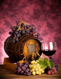 Red wine bottle and wine glass on wodden barrel. Red wine bottle with white and red grapes Stock Image