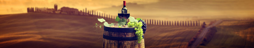 Red wine bottle and wine glass on wodden barrel. Beautiful Tusca. Ny background Stock Photo