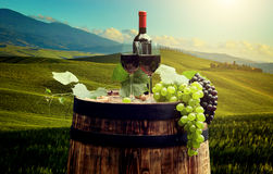 Red wine bottle and wine glass on wodden barrel Royalty Free Stock Photo