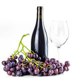 Red wine bottle, wineglass and grapes. Royalty Free Stock Photo