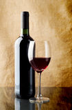 Red wine. In bottle and wineglass on linen background Royalty Free Stock Photos