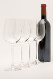 Red wine bottle with wineglasses lined up Stock Photography