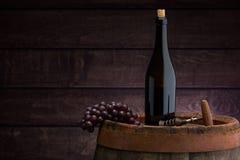 Red wine bottle  on wodden barrel. Red wine bottle and wine glass on wodden barrel royalty free stock images