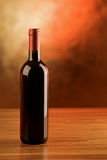 Red wine bottle on wooden table and golden background Royalty Free Stock Images