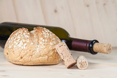 Red wine bottles with corks and bread on wooden Stock Images