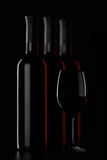 Red wine bottles and glass on dark background Stock Photography