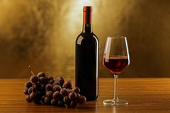 Red wine bottles with glass and grapes on wooden table and gold background Stock Image