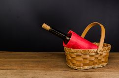 Red wine bottles on wicker basket on wooden table. Red wine bottles on wicker basket on wooden board and black background Stock Image