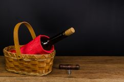 Red wine bottles on wicker basket on wooden table. Red wine bottles on wicker basket on wooden board and black background Stock Photos
