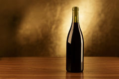 Red wine bottles wooden table and gold background Stock Photos