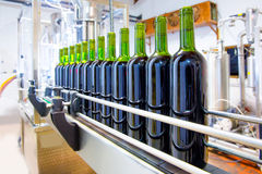 Red wine in bottling machine at winery. Red wine in glass bottling machine at winery Stock Photography