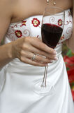 Red wine in bride hand. The hand of the bride in the white dress decorated by a red embroidery, holds a glass with red wine Stock Photos