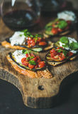 Red wine, brushetta with vegetables, cream-cheese and arugula Stock Photos
