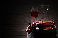 Red wine and a bunch of grapes on barrel. Red wine and a bunch of grapes on a wooden barrel royalty free stock images
