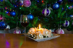 Red wine and candle on table with Christmas tree Stock Photos