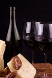 Red wine and cheese. Still life composition of red wine glasses and bottle, cheese chunks and sausage slices Royalty Free Stock Photos