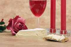 Red wine, cheese, cracker, candles and rose Royalty Free Stock Images