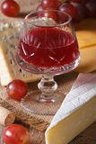 Red wine with cheese and grapes close-up vertical Royalty Free Stock Image