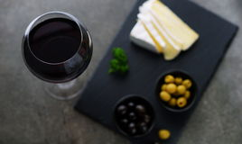 Red wine, cheese, olives. On a dark background Royalty Free Stock Photography