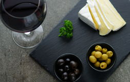 Red wine, cheese, olives. On a dark background Stock Images