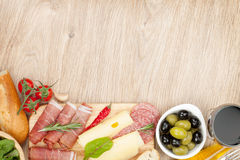 Red wine with cheese, olives, tomatoes, prosciutto, bread and sp Royalty Free Stock Photography