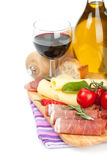 Red wine with cheese, prosciutto, bread, vegetables and spices Stock Image