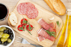 Red wine with cheese, prosciutto, bread, vegetables and spices Royalty Free Stock Image