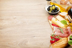 Red wine with cheese, prosciutto, bread, vegetables and spices Royalty Free Stock Images