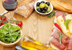 Red wine with cheese, prosciutto, bread, vegetables and spices Stock Photography