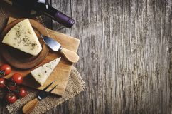 Red wine and cheese on rustic wooden board royalty free stock image
