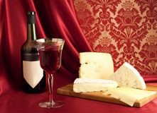 Red wine and cheese varieties. Single glass of red wine, cheese varieties on a cheeseboard Royalty Free Stock Photography