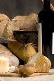 Red Wine with Chesse and Bread. A glass of red wine with an assorment of breads and cheeses Stock Image