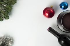 Red wine for Christmas. A bottle and a glass of red wine on a christmas decorated background Stock Image