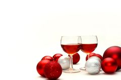 Red Wine and Christmas Decorations Isolated on White Background. Two wine glasses filled with red wine sit on an isolated white background surrounded by silver Royalty Free Stock Image
