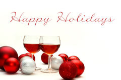 Red Wine and Christmas Decorations with Words Happy Holidays. Two wine glasses filled with red wine sit on an isolated white background with Happy Holidays Text Stock Images