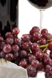 Red wine and closeup on grapes. Picture of some grapes and a piece of brie with red wine in the background royalty free stock images