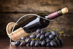 Red wine with cluster of dark blue grapes at wooden table. Stock Photos